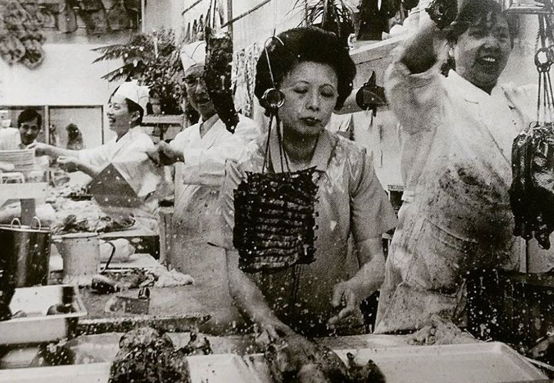 An black and white archival photo of an Asian woman in uniform works at the window of a Chinatown BBQ business