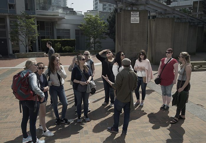 A walking tour group gathers around a tour guide in Chinatown